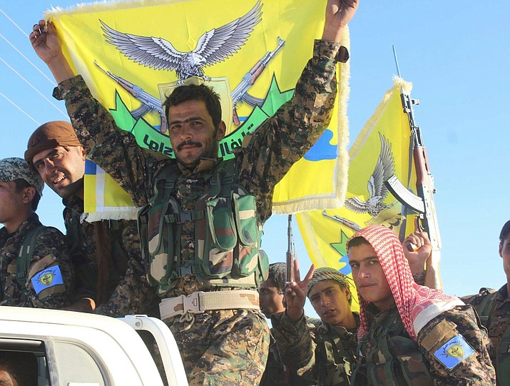 In this October 2016 photo, fighters of the Euphrates Liberation Brigade, part of the Manbij Military Council of the Syrian Democratic Forces, hold flags high in the city of Manbij in northern Syria. Syria's military said Friday it had entered the key Kurdish-held town of Manbij in an apparent deal with the Kurds, who are looking for new allies and protection against a threatened Turkish offensive as U.S. troops prepare to leave Syria. (Photo by Kurdishstruggle [CC BY 2.0 (https://creativecommons.org/licenses/by/2.0)], via Wikimedia Commons)
