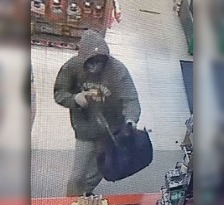 In an image taken from a security camera, the suspect in the Quick Stop armed robbery is pictured. The man wore a bandana and sunglasses. He had a gray 'Ecko Unltd' hooded sweatshirt, light colored pants and white shoes, and was approximately 5-foot-6 to 5-foot-8 and of medium build. (PPD/Courtesy)