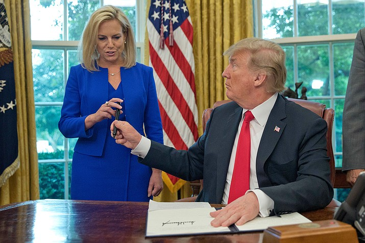 In this Wednesday, June 20 file photo, President Donald Trump gives the pen he used to sign the executive order to end family separations to Homeland Security Secretary Kirstjen Nielsen during an event in the Oval Office of the White House in Washington. (Pablo Martinez Monsivais/AP)
