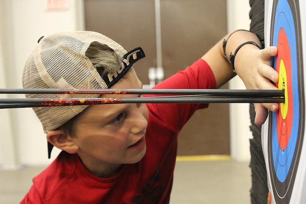 June 20 – Hayden Gonzales, 11, counts the points on his target at Inside Out Archery. Corbin and Brad Rowden host weekly shooting sessions at the Mohave County Fairgrounds.