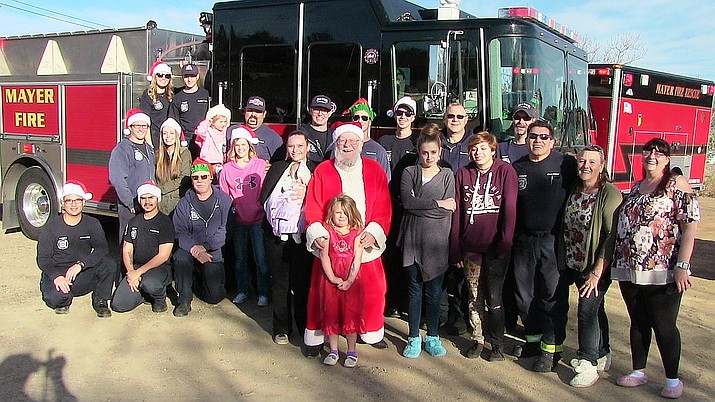 Santa and members of the Mayer Firefighter Charities community pose Monday, Dec. 24, 2018, as firefighters deliver presents to Jay West and her children, Heather, 15, Jaylee, 12, Rylee, 5, and Emalee, 2 months. (Courtesy)