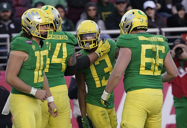 Oregon wide receiver Dillon Mitchell (13) celebrates with Brady Aiello (66) and Calvin Throckmorton (54) after scoring a touchdown against Michigan State during the second half of the Redbox Bowl NCAA college football game Monday, Dec. 31, 2018, in Santa Clara, Calif. Oregon won 7-6. (Tony Avelar/AP)