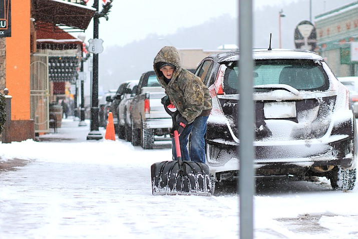 "Jace Maebe takes care of shoveling in front of his parent's business, Brewed Awakenings, on Route 66 in Williams Dec. 31. The National Weather Service forecasts 4-6"" of snow for Williams."