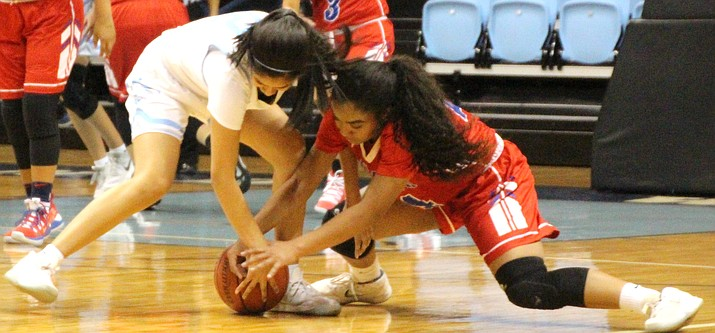 Window Rock Fighting Scout's Asia James (right) battles Holbrook's Madison Chappell for possession of a loose ball in a game held at the Bee Ho'ldzil Fighting Scouts Event center. (Anton Wero/NHO)