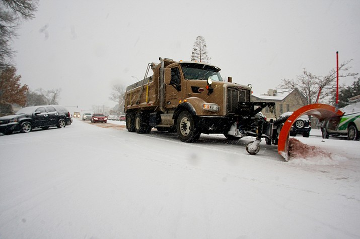 A City of Prescott snowplow clears the snow and applies a cinder treatment to Marina Street near the corner of Willis Monday morning. The fast-accumulating snow caused a number of traffic jams on downtown streets on New Year's Eve Day, Dec. 31. (Cindy Barks/Courier)