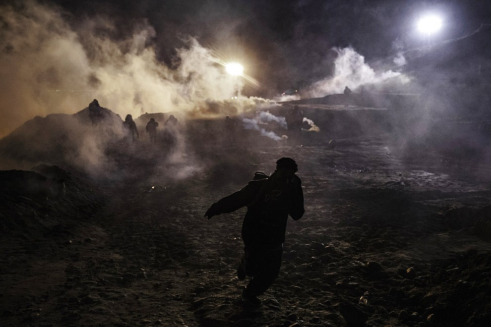 Migrants run as tear gas is thrown by U.S. Border Protection officers to the Mexican side of the border fence after they climbed the fence to get to San Diego, Calif., from Tijuana, Mexico, Tuesday, Jan. 1, 2019. Discouraged by the long wait to apply for asylum through official ports of entry, many migrants from recent caravans are choosing to cross the U.S. border wall and hand themselves in to border patrol agents. (AP Photo/Daniel Ochoa de Olza)
