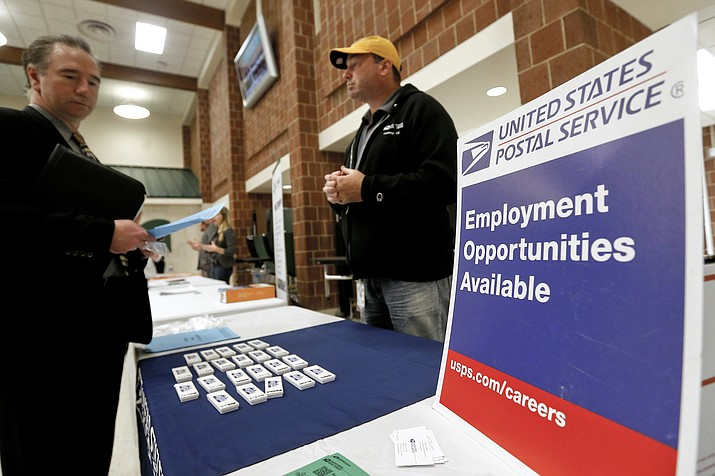 In this Nov. 2, 2017, file photo a recruiter from the postal service, right, speaks with an attendee of a job fair in the cafeteria of Deer Lakes High School in Cheswick, Pa. Even with fear of a global economic slump depressing stock markets, Friday, Jan. 4, 2019 jobs report for December is expected to offer reassurance that the U.S. economy remains sturdy and on track to expand for a 10th straight year. (Keith Srakocic/AP, File)