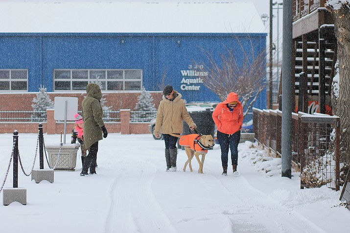 Visitors walk through town during the New Year's Eve snow storm.