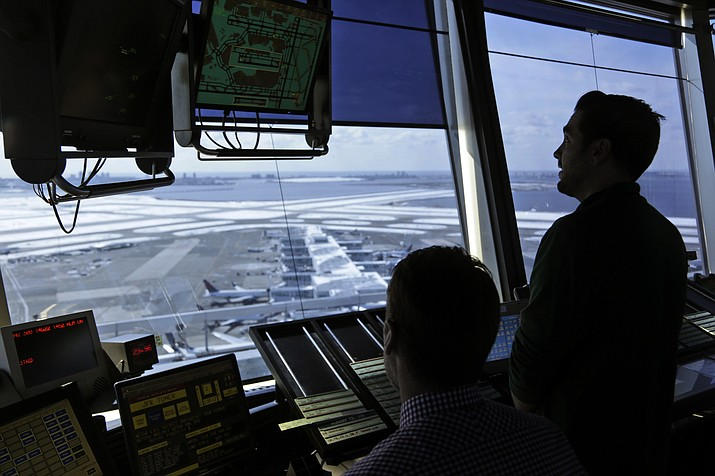 In this March 16, 2017, file photo, air traffic controllers work in the tower at John F. Kennedy International Airport in New York. The partial government shutdown is starting to effect air travelers. Over the weekend, some airports had long lines at checkpoints, apparently caused by a rising number of security officers calling in sick while they are not getting paid. (AP Photo/Seth Wenig, File)