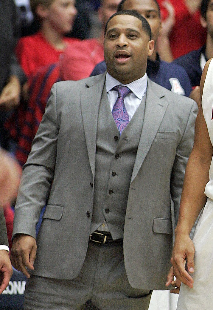 In this Dec. 11, 2013, file photo, Arizona's assistant coach Emanuel Richardson watches from the sideline during the second half of an NCAA college basketball game against New Mexico State in Tucson, Ariz. Richardson was identified in court papers, and is among 10 people facing federal charges in Manhattan federal court, Tuesday, Sept. 26, 2017, in a wide probe of fraud and corruption in the NCAA, authorities said (John Miller/AP, file)