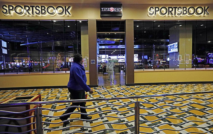 A In this Dec. 18, 2018 photo, a woman walks by the Time Out Lounge at the Pearl River Resort, in Philadelphia, Mississippi. The sports book owned by the Mississippi Band of Choctaw Indians is the first to open on tribal lands outside of Nevada following a U.S. Supreme Court ruling earlier this year, a no-brainer business decision given the sports fans among its gambling clientele. (AP Photo/Rogelio V. Solis)