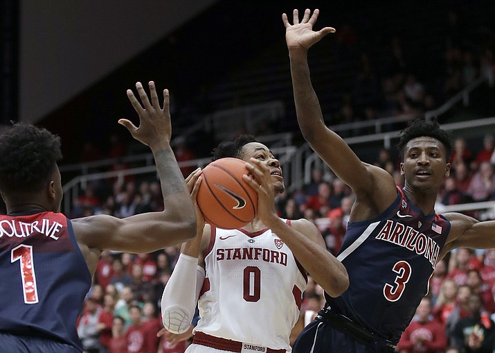 Stanford forward KZ Okpala (0) shoots between Arizona guards Devonaire Doutrive (1) and Dylan Smith (3) during the first half of an NCAA college basketball game in Stanford, Calif., Wednesday, Jan. 9, 2019. (Jeff Chiu/AP)