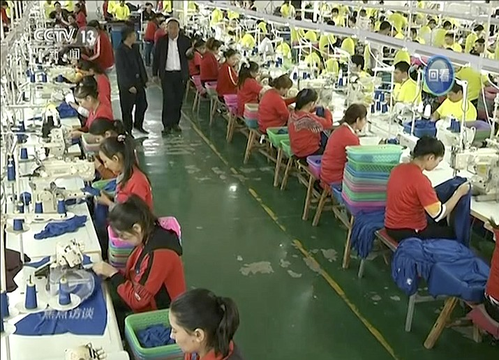 In this file image from undated video footage run by China's CCTV via AP Video, Muslim trainees work in a garment factory at the Hotan Vocational Education and Training Center in Hotan, Xinjiang, northwest China. (CCTV via AP Video, File)