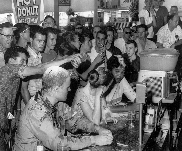 In this May 28, 1963 file photo, a group of whites pour sugar, ketchup and mustard over the heads of Tougaloo College student demonstrators at a sit-in demonstration at a Woolworth's lunch counter in Jackson, Miss. Seated at the counter, from left, are Tougaloo College professor John Salter,and students Joan Trumpauer and Anne Moody. John Salter, who also used the name John Hunter Gray, died Monday, Jan. 7, 2019 at his home in Pocatello, Idaho. Relatives say he was 84 when he died Monday after an illness. (Fred Blackwell/The Clarion-Ledger via AP, file)