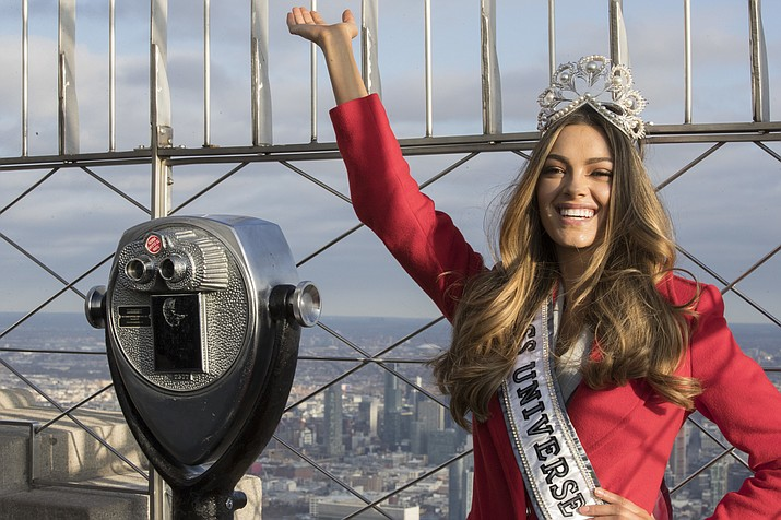 In this Tuesday, Nov. 28, 2017 file photo, Miss Universe 2017 Demi-Leigh Nel-Peters, of South Africa, poses for photographers on the 86th Floor Observation Deck of the Empire State Building in New York. Former Denver Broncos and University of Florida quarterback Tim Tebow is engaged. The Heisman Trophy winner announced his engagement on Instagram Thursday, Jan. 10, 2019 to Demi-Leigh Nel-Peters, a South Africa native and the 2017 Miss Universe. (Mary Altaffer/AP, file)