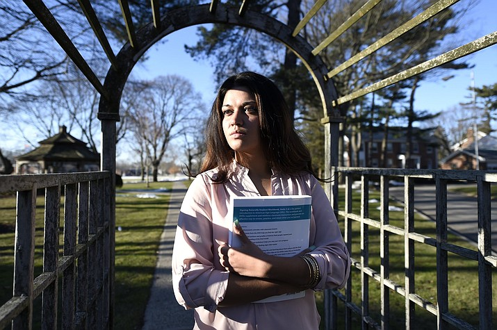In this Feb. 2, 2016, file photo, Naila Amin, 26, holds a book from one of the classes she was taking at Nassau Community College in Garden City, N.Y. According to data provided to The Associated Press, the U.S. approved thousands of requests by men to bring child and teenage brides from another country.  (AP Photo/Kathy Kmonicek)