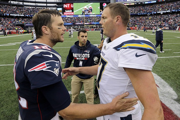 In this Oct. 29, 2017, file photo, New England Patriots quarterback Tom Brady (12) and Los Angeles Chargers quarterback Philip Rivers (17) speak at midfield after an NFL football game, in Foxborough, Mass. The Chargers and Patriots meet in a divisional playoff game on Sunday, Jan. 13, 2019. (Steven Senne/AP, File)