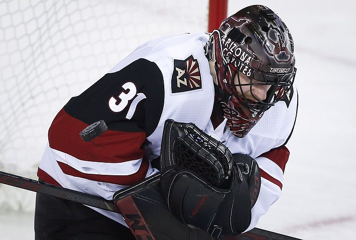 Arizona Coyotes goalie Adin Hill loses the puck during the first period against the Calgary Flames, Sunday, Jan. 13, 2019, in Calgary, Alberta. (Jeff McIntosh/The Canadian Press via AP)