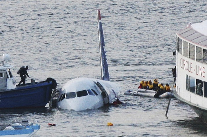 """In this Jan. 15, 2009 file photo, a diver, left, aboard an NYPD vessel prepares to rescue passengers that escaped from the Airbus 320 US Airways aircraft made an emergency landing in the Hudson River in New York in what came to be known as the """"Miracle on the Hudson"""" because everyone survived. It's been 10 years since US Airways flight 1549 landed on the Hudson River after colliding with a flock of geese just after takeoff. (AP Photo/Bebeto Matthews, File)"""