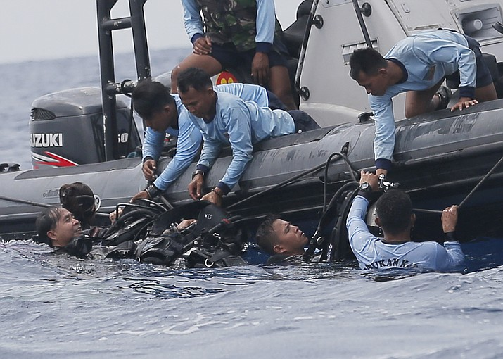 Indonesian navy frogmen emerge from the water Oct. 30, 2018, during a search operation for the victims of the crashed Lion Air plane in the waters of Tanjung Karawang, Indonesia. (Tatan Syuflana/AP, File)
