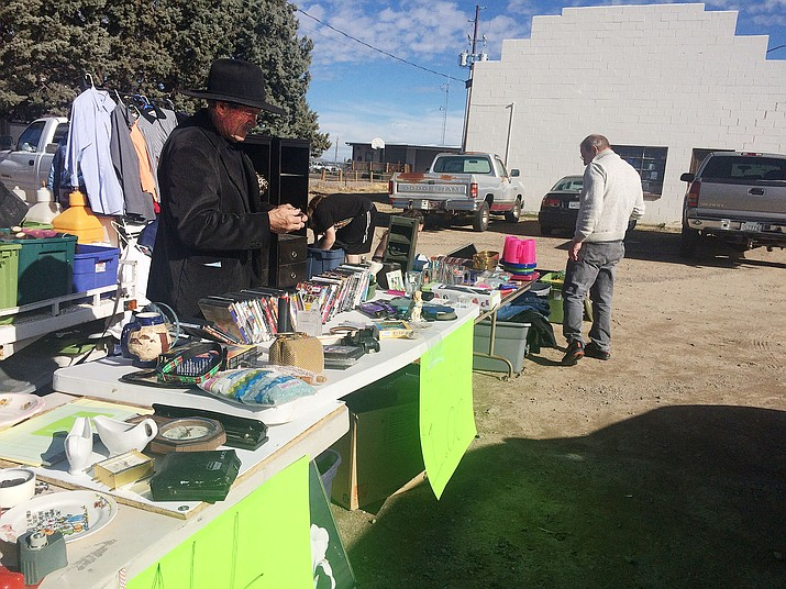 Interested bargain hunters peruse a $1 sale put on by Jeff Baldwin near Doug's Gas Station. The items were from abandoned storage units, and Baldwin says he puts the sale on about once per week, and he plans on holding the sales in a central location soon. (Jason Wheeler/Review)