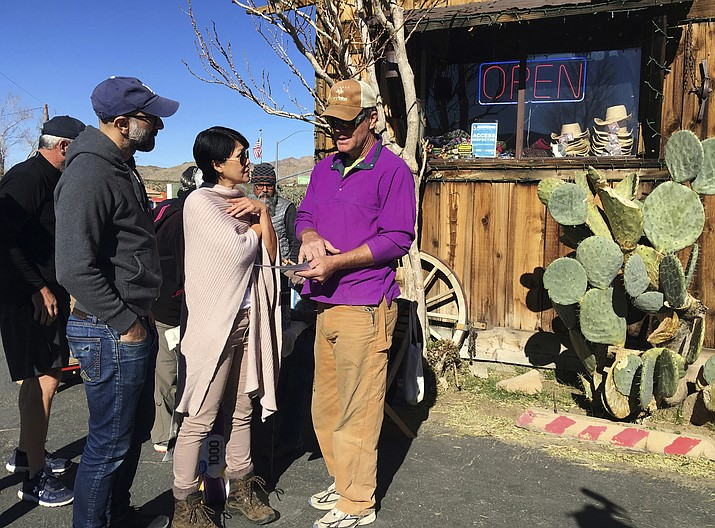 John Lauretig, executive director of Friends of Joshua Tree, talks to visitors at Coyote Corner, outside the entrance to Joshua Tree National Park in the southern California desert Thursday, Jan. 3, 2019. (AP Photo/Krysta Fauria)