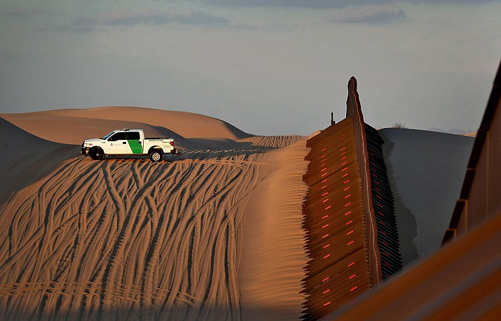A U.S. Customs and Border Patrol agent patrols a section of floating fence that runs through Imperial Sand Dunes along the international border with Mexico at sunset July 18, 2018, in Imperial County, Calif. (Matt York/AP, File)