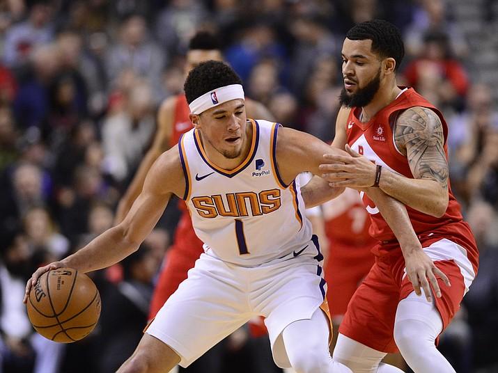 Phoenix Suns guard Devin Booker (1) shields the ball from Toronto Raptors guard Fred VanVleet (23) during the first half of an NBA basketball game Thursday, Jan. 17, 2019, in Toronto. (Frank Gunn/The Canadian Press via AP)