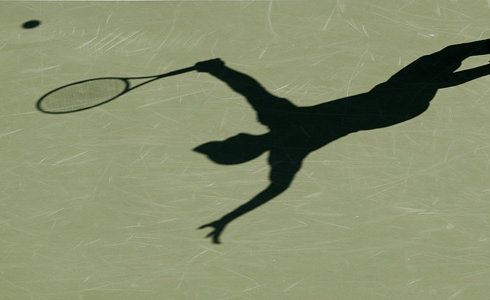 FILE - This is a 2017 file photo showing the shadow of a tennis player. Four people are in French custody on suspicion of fixing matches for an Armenian based in Belgium believed behind an illegal gambling syndicate suspected of fixing hundreds of matches. It's part of months of digging by police working across Europe to unravel a match-fixing scheme of breath-taking scale involving more than 100 players from at least half a dozen countries.