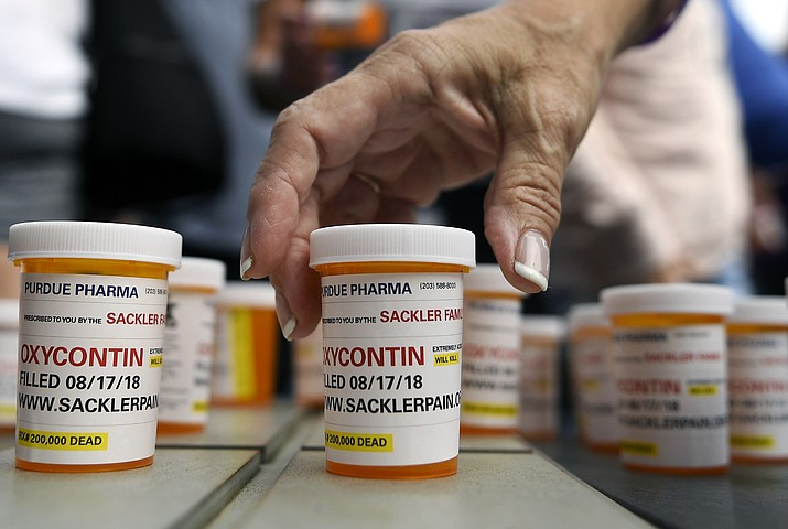 Family and friends who have lost loved ones to OxyContin and opioid overdoses leave pill bottles in protest Aug. 17, 2018, outside the headquarters of Purdue Pharma, which is owned by the Sackler family, in Stamford, Conn. (Jessica Hill/AP)