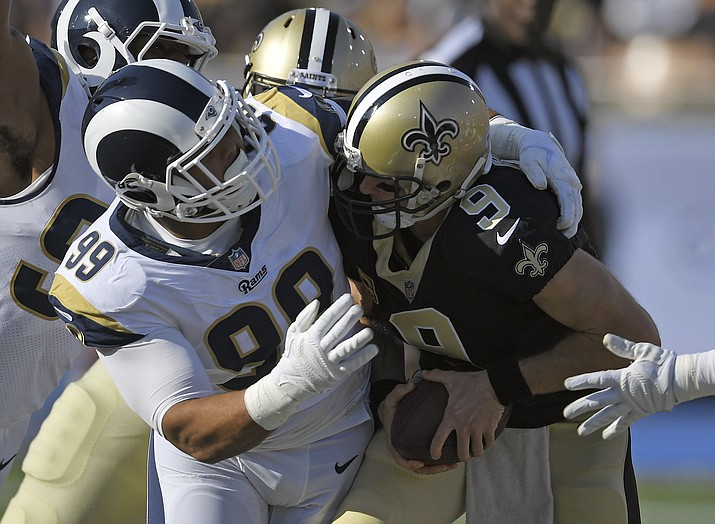 In this Nov. 26, 2017, file photo, New Orleans Saints quarterback Drew Brees, right, gets sacked by Los Angeles Rams defensive end Aaron Donald during the first half of an NFL football game, in Los Angeles. The Rams, with unanimous All-Pro defensive tackle Aaron Donald take on the Saints in the NFC Championship on Sunday, Jan. 20, 2019.(Mark J. Terrill/AP, file)
