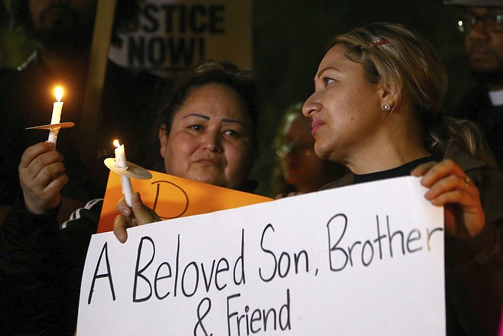 Sandra Gonzalez, left, mother of slain 14-year-old boy shot by Tempe Police, joins another family member, right, and others in front of the Tempe Police headquarters to hold a protest and vigil for the boy shot to death as police say they were pursuing a burglary suspect who they thought had a handgun, Thursday, Jan. 17, 2019, in Tempe, Ariz. It turns out, according to police, the teen had a replica gun. (AP Photo/Ross D. Franklin)