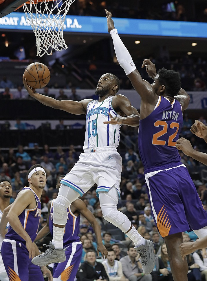 Charlotte Hornets' Kemba Walker (15) drives past Phoenix Suns' Deandre Ayton (22) during the first half of an NBA basketball game in Charlotte, N.C., Saturday, Jan. 19, 2019. (Chuck Burton/AP)