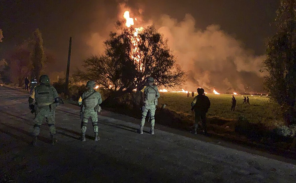 In this image provided by the Secretary of National Defense, soldiers guard the area by an oil pipeline explosion in Tlahuelilpan, Hidalgo state, Mexico, Friday, Jan. 18, 2019. A huge fire exploded at a pipeline leaking fuel in central Mexico on Friday, killing at least 21 people and badly burning 71 others as locals were collecting the spilling gasoline in buckets and garbage cans, officials said. Officials said the leak was caused by an illegal tap that fuel thieves had drilled into the pipeline in a small town in the state of Hidalgo, about 62 miles (100 kilometers) north of Mexico City. (Secretary of National Defense via AP)