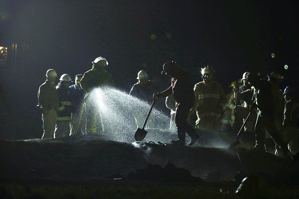 Staff of Pemex, Petroleos Mexicanos, works the area of a oil pipeline explosion in Tlahuelilpan, Hidalgo state, Mexico, Saturday, Jan. 19, 2019. A massive fireball that engulfed people scooping up fuel spilling from a pipeline ruptured by thieves in central Mexico killed several people and badly burned others.  (AP Photo/Claudio Cruz)