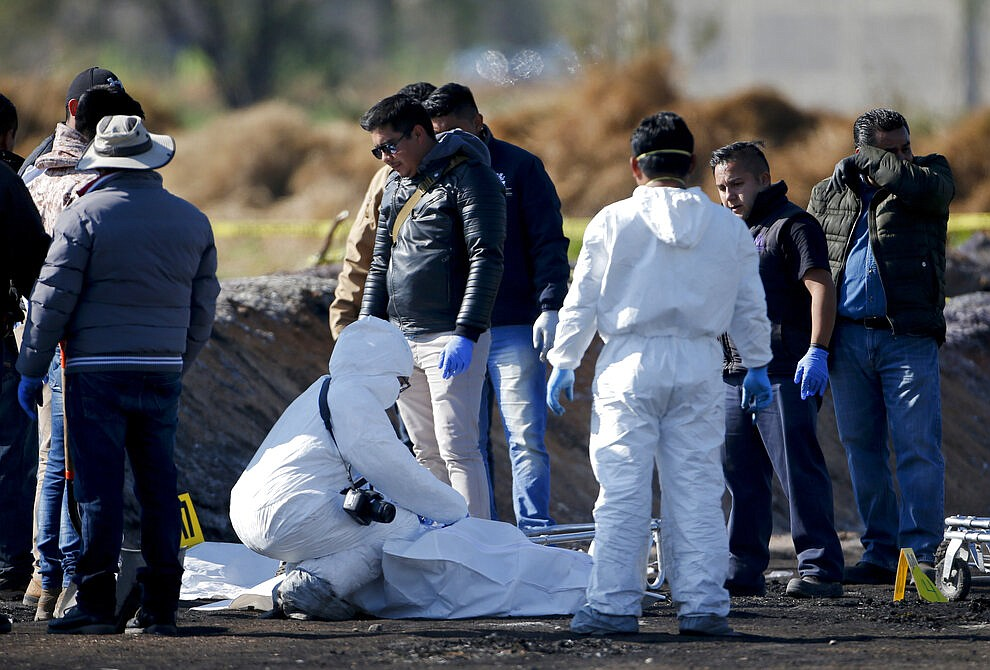 Forensic experts working in the area an oil pipeline explosion in Tlahuelilpan, Hidalgo state, Mexico, Saturday, Jan. 19, 2019. A massive fireball that engulfed people scooping up fuel spilling from a pipeline ruptured by thieves in central Mexico killed dozens of people and badly burned many more.  (AP Photo/Claudio Cruz)