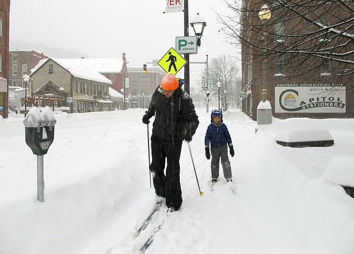 Nicholas Nicolet and his son Rocco cross-country ski on Sunday, Jan. 20, 2019, in Montpelier, Vt. A major winter storm that blanketed most of the Midwest with snow earlier in the weekend barreled toward New England Sunday, where it was expected to cause transportation havoc ranging from slick and clogged roads to hundreds of cancelled airline flights. (AP Photo/Lisa Rathke)