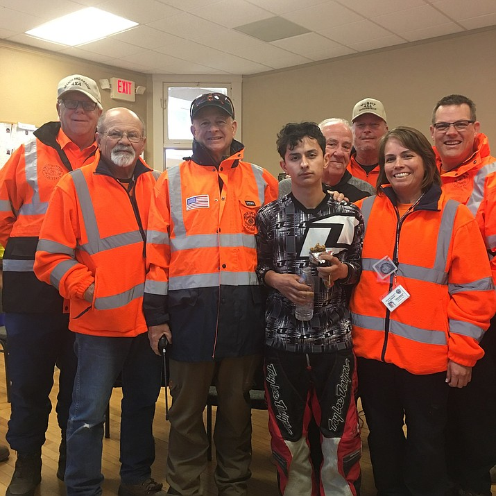 Jhon Zuluaga Ossa, 18, stands with members of the Yavapai County Search and Rescue Team after being found walking along Forest Road 362 near Crown King Monday morning, Jan. 21. The young man was riding an ATV in the area when he got lost and ran out of gas.
