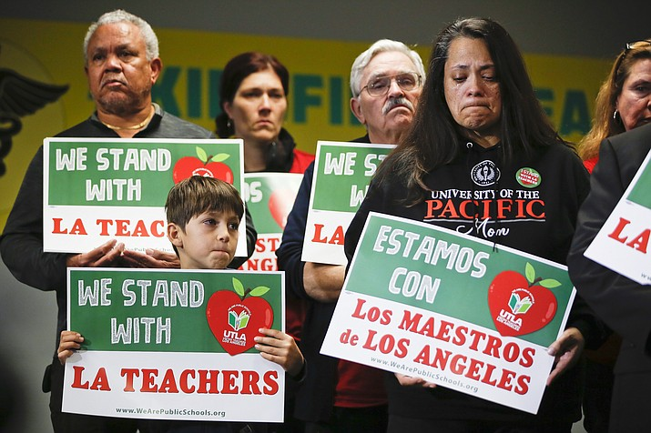 In this Jan. 13, 2019, file photo, student Leo Rittner Solomon, 6, front left, and parent Hilda Rodriguez Guzman, right, react as United Teachers Los Angeles president and teacher Alex Caputo-Pearl announces the nation's second-largest school district, Los Angeles Unified School District, was going on strike in Los Angeles. The union said Monday, Jan. 21, that teachers are due back at picket lines Tuesday morning even if an agreement is reached Monday, saying it takes time to mobilize a ratification vote of a deal. (AP Photo/Damian Dovarganes, File)