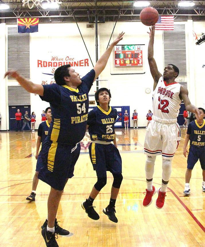 Holbrook Roadrunners' Jeffery Jones attempts a jump shot over Valley Pirates Marcellue Barney and Tristan Store (25), in a non-sectional game, at the Tony Munoz Gym in Holbrook, Ariz. Holbrook won the contest, 70 to 39 over the Valley Pirates. (Anton Wero/NHO)