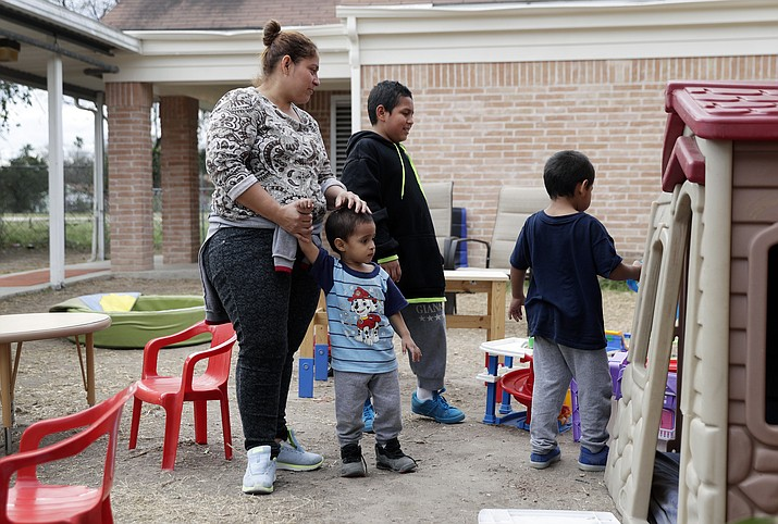 In this Friday, Jan. 11, 2019, photo, Maria Orbelina Cortez stands with her three sons, ages 11, 5, and 3, in the yard behind the Catholic Charities shelter in McAllen, Texas. Orbelina says that after fleeing El Salvador, she hopes to find refuge for her children with her parents in California. (AP Photo/Eric Gay)