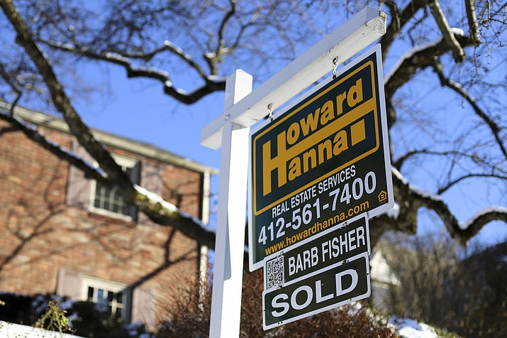 This Monday, Jan. 14, 2019, photo, shows a sign outside a home that has been sold, in Mount Lebanon, Pa. Home sales in many areas of the country have dipped, and prices gains have slowed. Yet a rising number of middle-class Americans have been priced out of their home markets. (AP Photo/Gene J. Puskar)