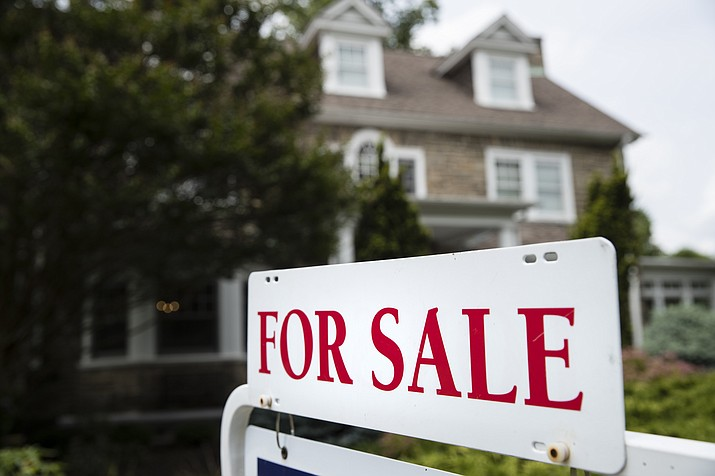 "In this Friday, June 8, 2018, photo, a ""For Sale"" sign stands in front of a house. Home sales in many areas of the country have dipped, and prices gains have slowed. Yet a rising number of middle-class Americans have been priced out of their home markets. (Matt Rourke, file)"