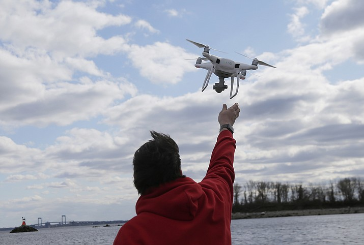 In this April 29, 2018, file photo, a drone operator helps to retrieve a drone after photographing over Hart Island in New York. Drone sightings reported by airline pilots over New Jersey renew questions about how to accommodate the popular devices into the nation's airspace. The ability of drones to interfere with aviation is likely to get worse as the number of machines multiplies. Many store-bought drones come with technology to prevent owners from flying them near airports, but there are hacks, and home-built machines don't necessarily include those protections. (AP Photo/Seth Wenig, File)