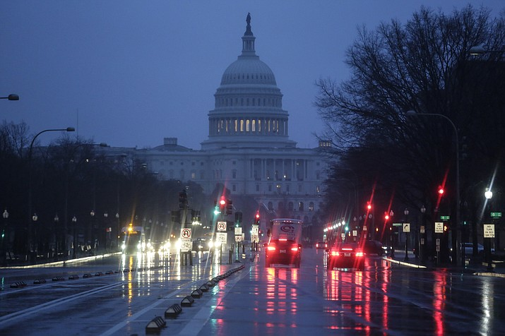 The Capitol is seen early Thursday, Jan. 24, 2019, as rain falls on Pennsylvania Avenue in Washington, with the partial government shutdown in its second month. The Senate will vote on two competing proposals today to end the impasse, but neither seems to have enough votes to advance. (AP Photo/J. Scott Applewhite)