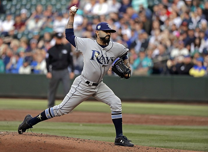 In this June 1, 2018, file photo, Tampa Bay Rays starting pitcher Sergio Romo throws to a Seattle Mariners batter during the first inning of a baseball game in Seattle. A person familiar with the negotiations tells The Associated Press that Major League Baseball has proposed going back to a 15-day disabled list and increasing the time optioned players usually must spend in the minor leagues. The moves are aimed at reducing the use of relief pitchers and reviving offense. (Ted S. Warren/AP, file)