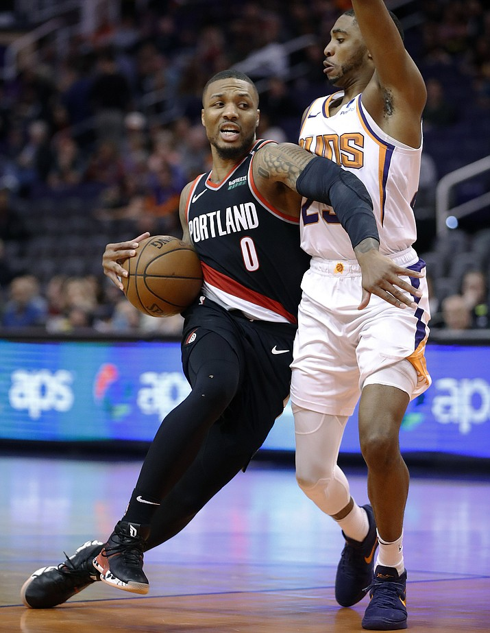 Portland Trail Blazers guard Damian Lillard (0) drives around Phoenix Suns forward Mikal Bridges during the second half of an NBA basketball game Thursday, Jan. 24, 2019, in Phoenix. (Matt York/AP)