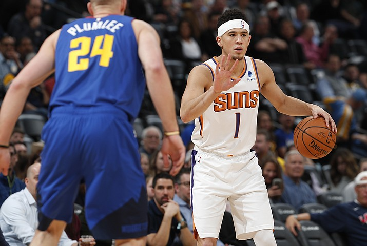 Phoenix Suns guard Devin Booker looks to pass the ball as Denver Nuggets forward Mason Plumlee defends in the first half of an NBA basketball game Friday, Jan. 25, 2019, in Denver. (David Zalubowski/AP)