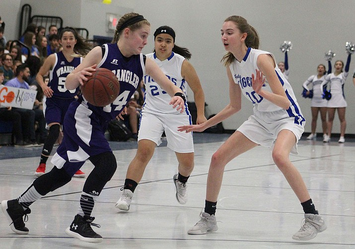 Kingman Academy's Erika Delgado, left, and Faith Edwards try to stop a Wickenburg player Friday in a 49-42 victory. (Photo by Beau Bearden/Daily Miner)