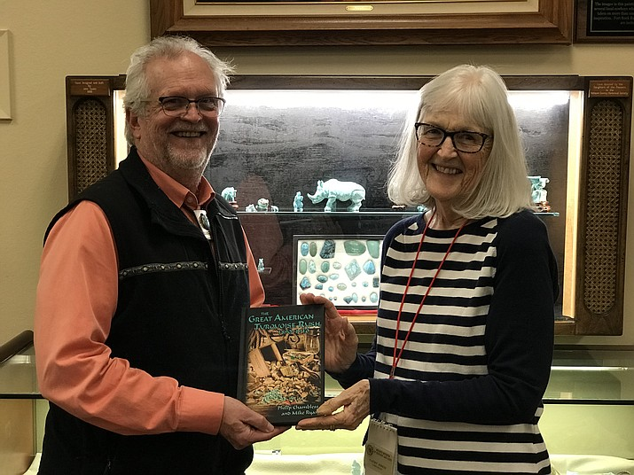 """Mike Ryan, left, presents a copy of the book he co-authored, """"The Great American Turquoise Rush,"""" to librarian Cathy Kreis at the Mohave Museum of History and Arts. (Courtesy photo)"""